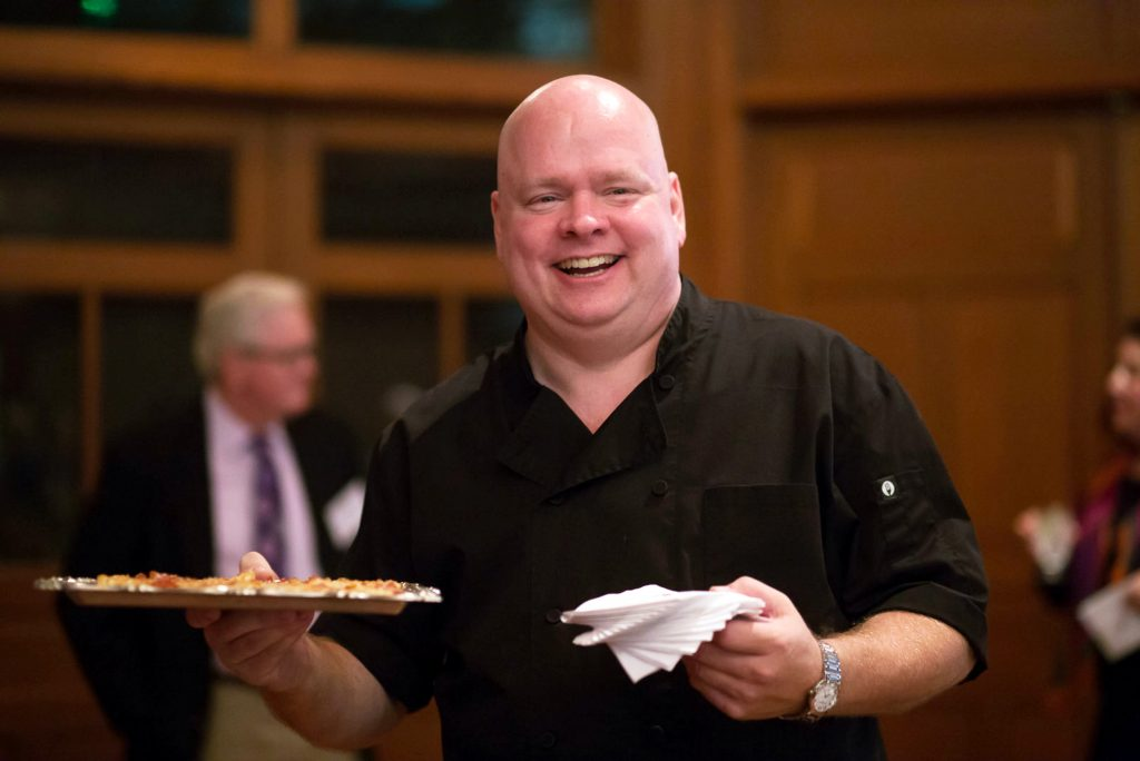 Keith Little smiling at the camera while holding a plate of food and napkins.